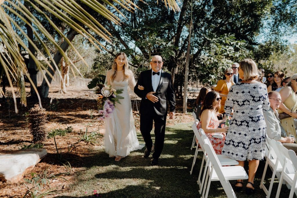 father walks his daughter down the aisle in their backyard in Broome Western Australia