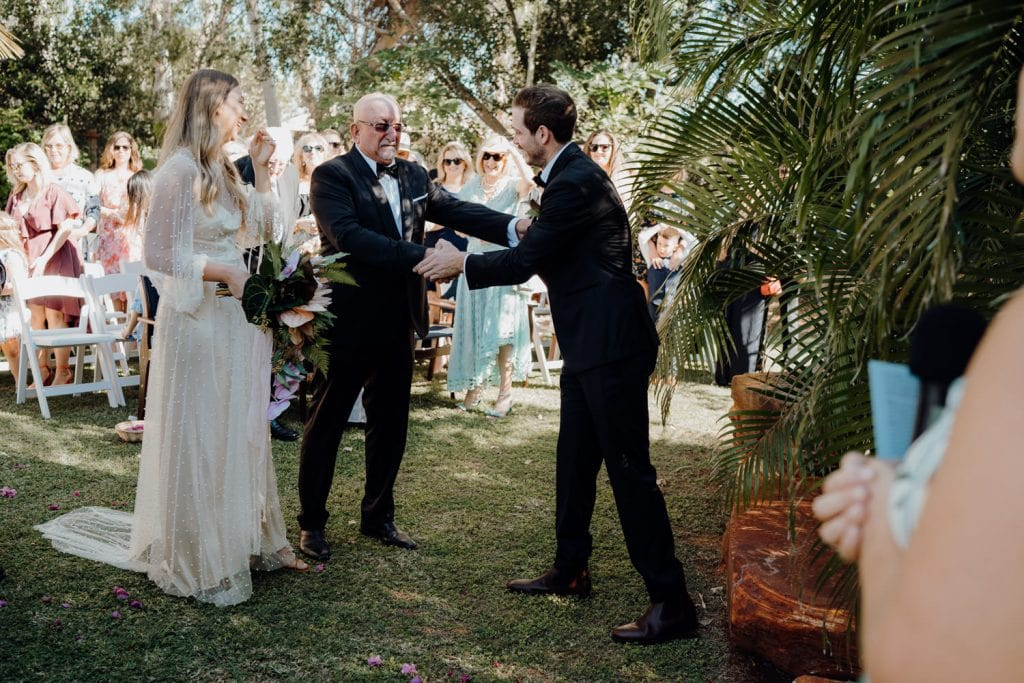 father of the bride shakes the groom's hand when passing on his daughter to be married
