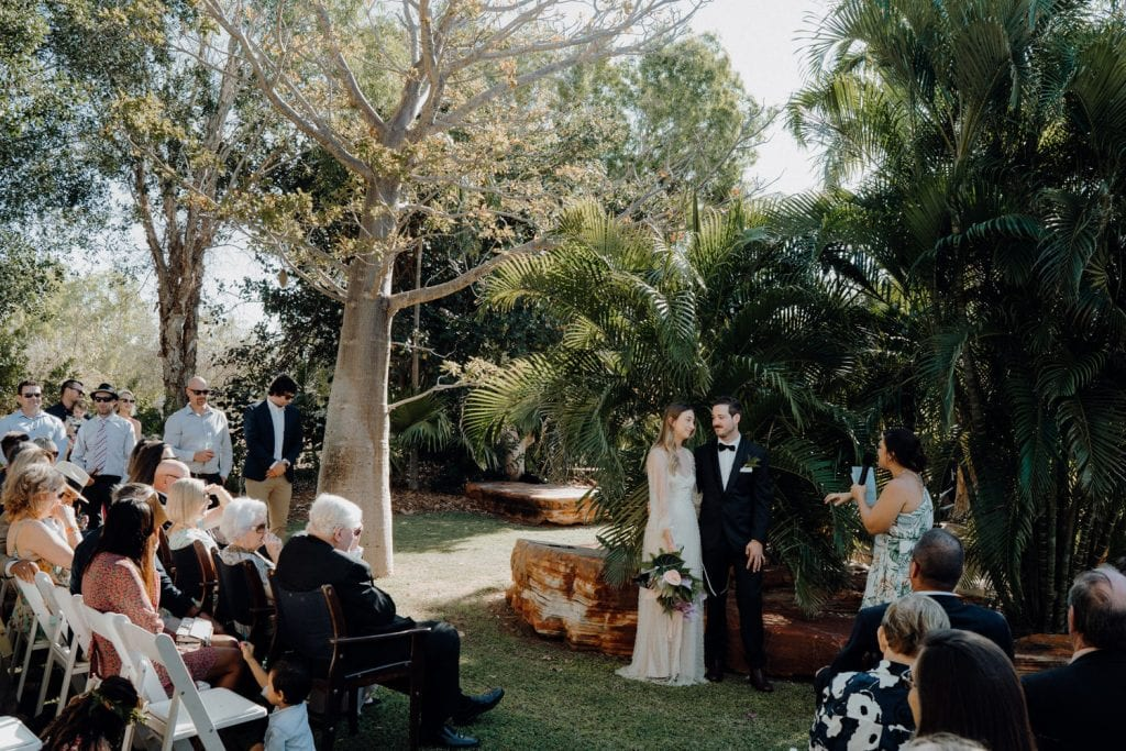 wide shot of wedding ceremony in backyard in Broome Western Australia with boab tree and guests seated