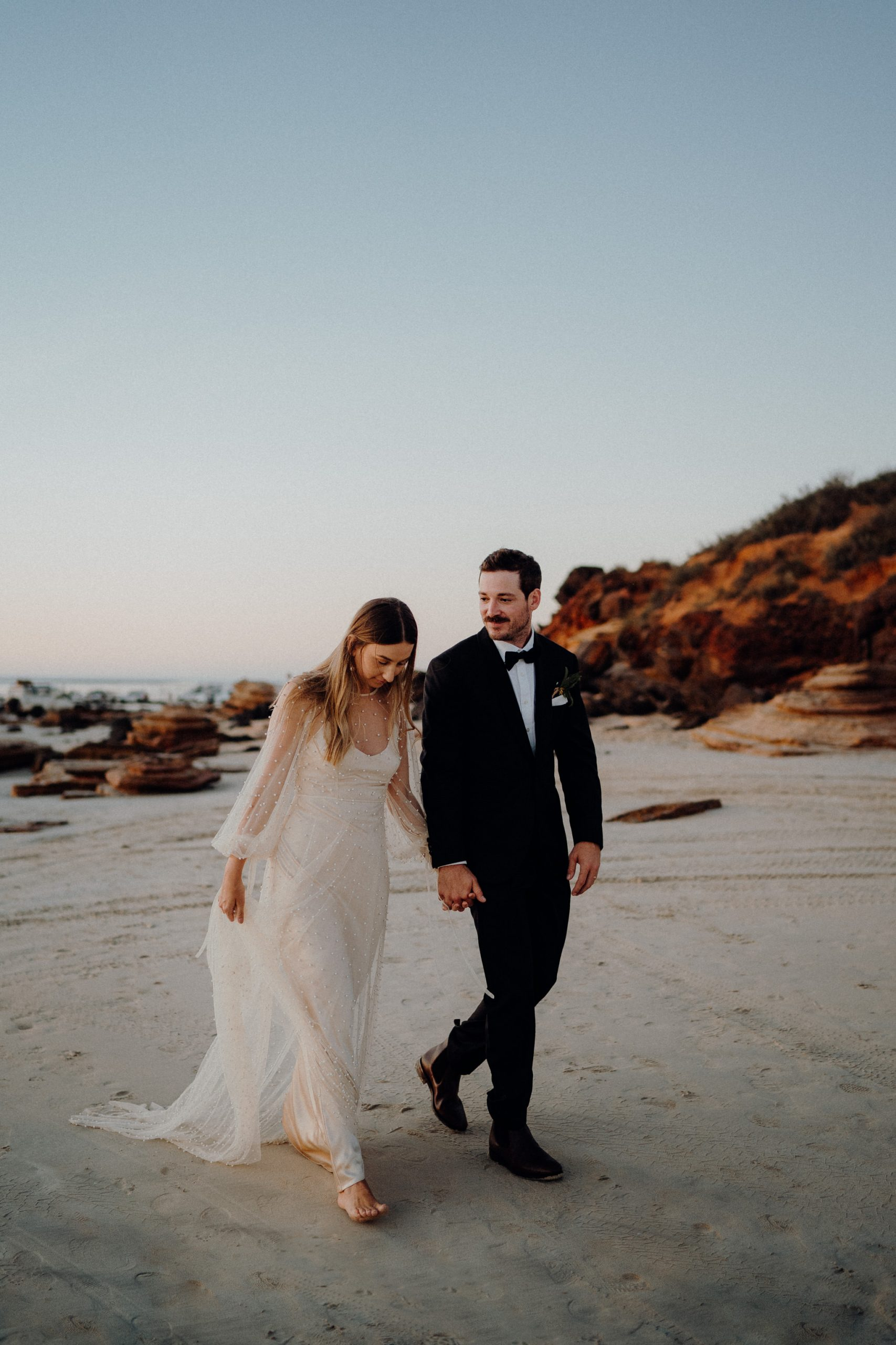 young wedding couple dressed up in suits and dress walking hand in hand on Cable Beach towards their wedding reception at Cable Beach Amphitheatre