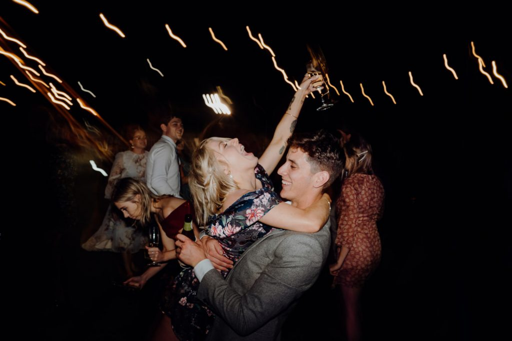 man and woman dancing and laughing with drinks in their hands