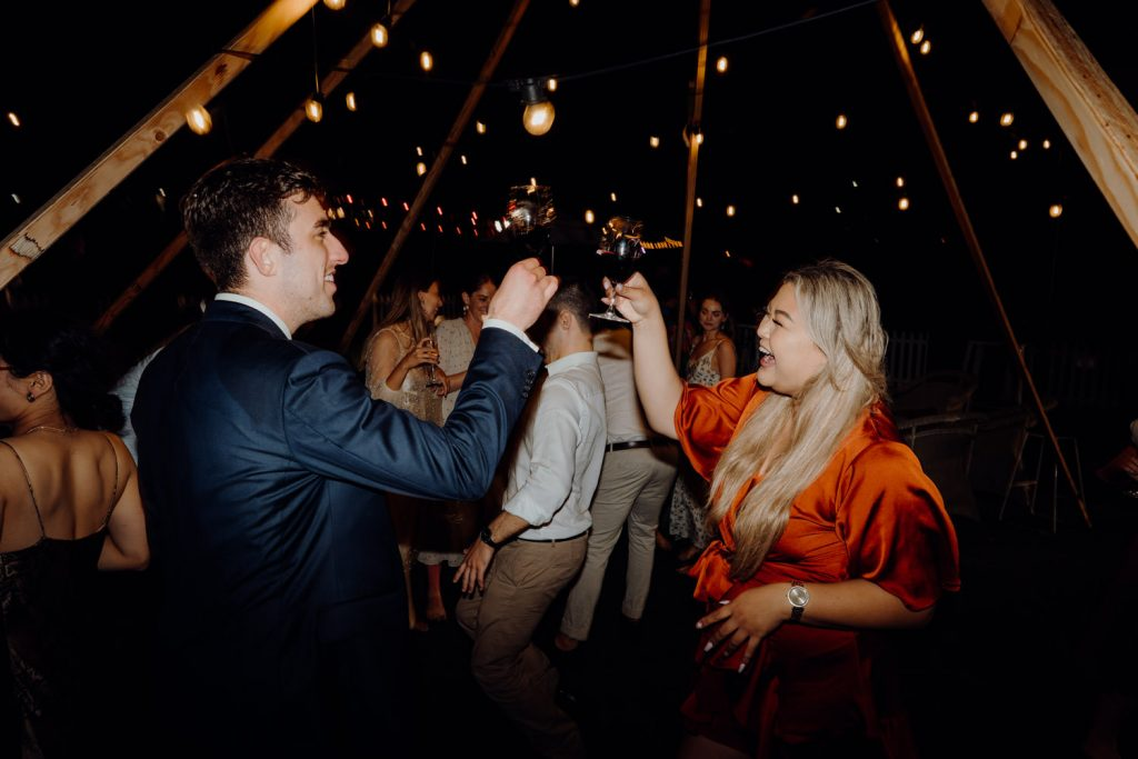 two wedding guests having a cheers with their wine glasses at Broome wedding with fairy lights surrounding them