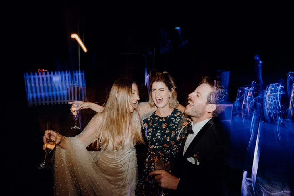 three people dancing on outdoor dancefloor with glasses of champagne in their hands and signing along to tunes