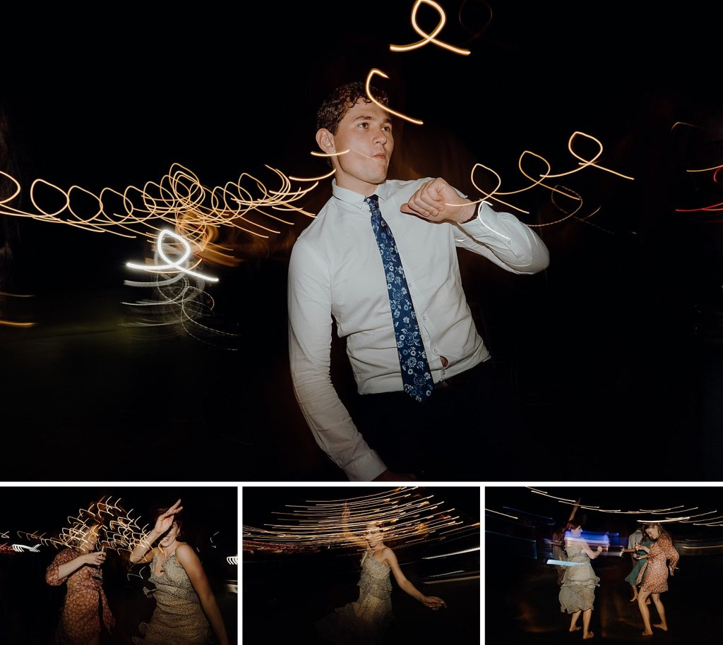 young man in shirt and tie dances at Cable Beach Amphitheatre wedding party with light trails around him cause by low shutter speed