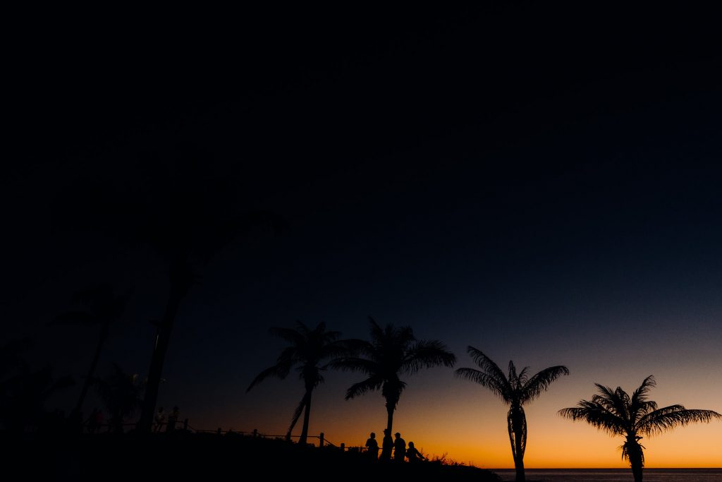 last light over Cable Beach with a shimmer of red still in the sky and palm trees as silhouettes