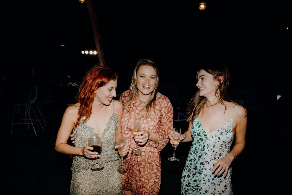 three women in summer dresses and drinks in their hands at Broome wedding