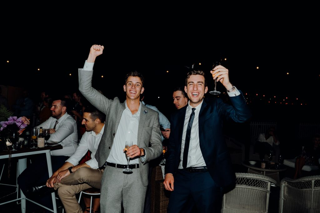 two man in suits cheering and laughing during wedding speeches