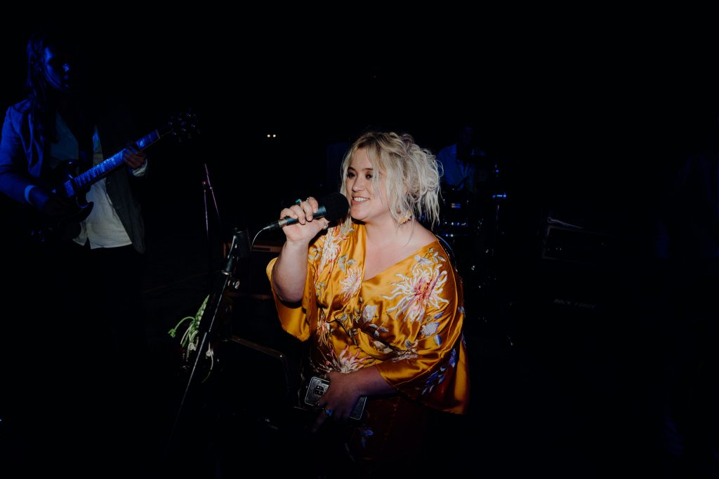 Ruby May Perth singer on the microphone in yellow dress
