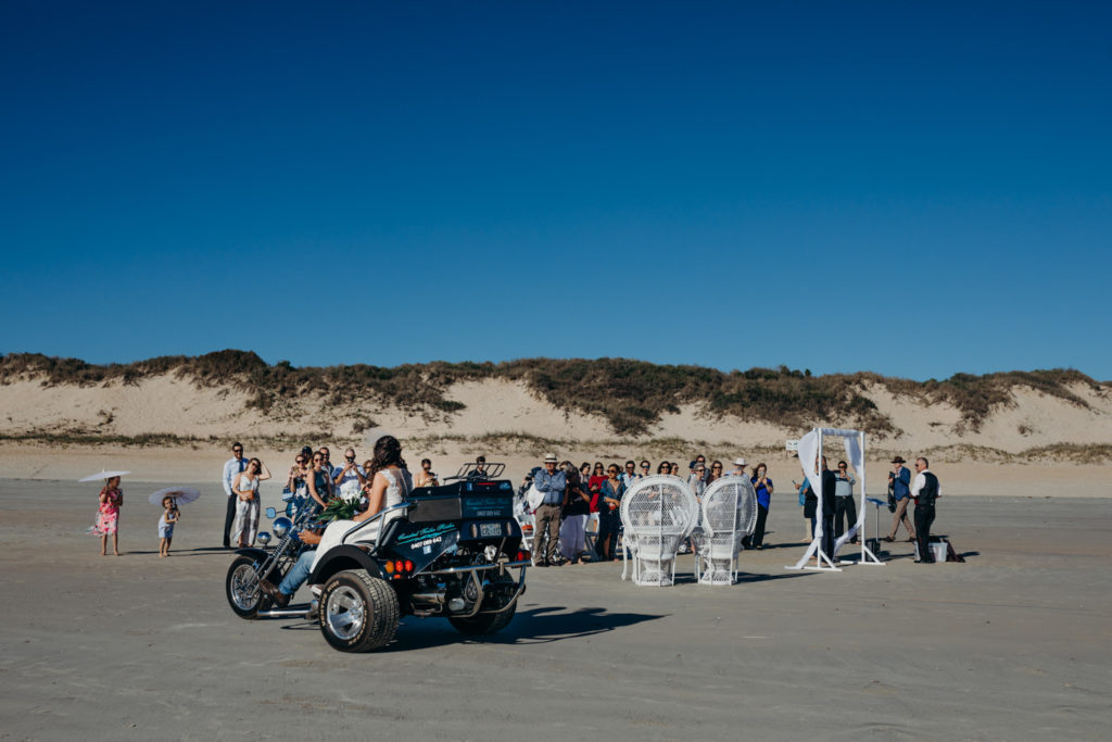 Bride arrives on motorbike to her Cable Beach Wedding in Broome Western Australia