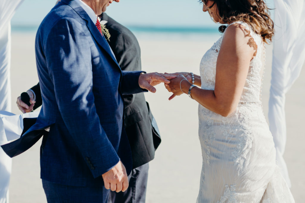 ring exchange on Cable Beach of bride and groom in wedding attire