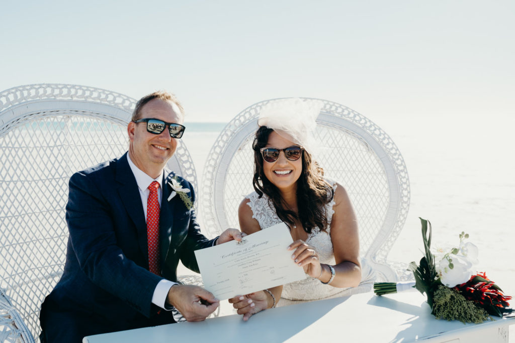 wedding couple sitting in white peacock chairs on the beach holding up their marriage certificate