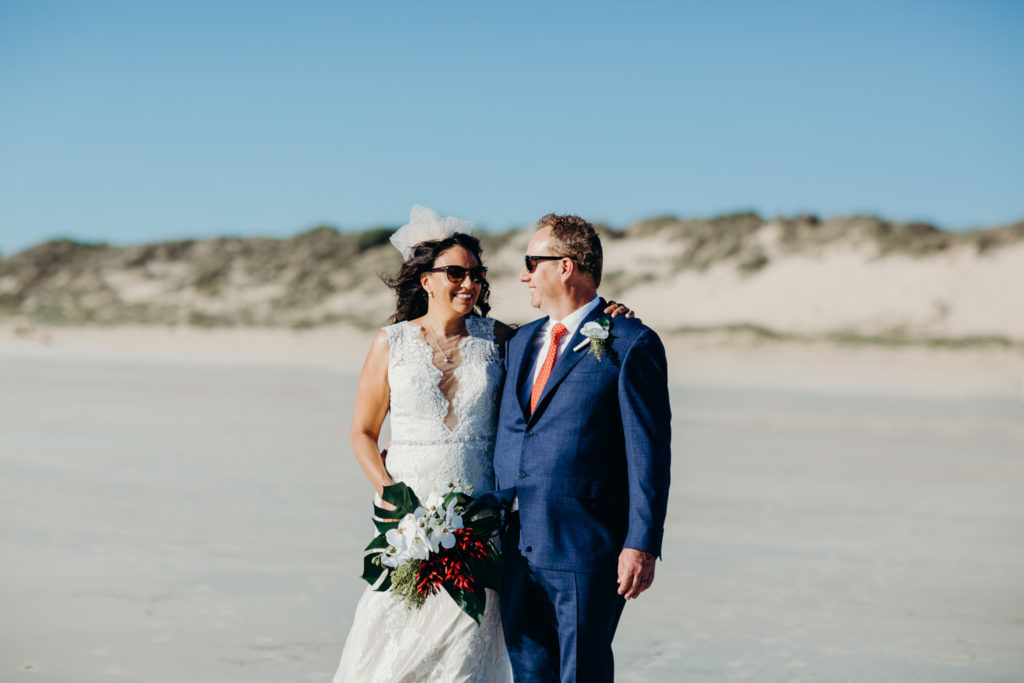freshly hitched couple standing arm in arm on Cable Beach in Broome after there ceremony