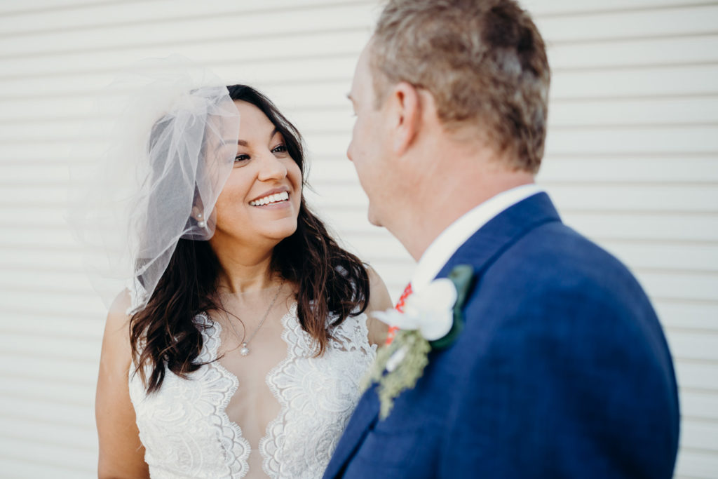 woman in wedding dress smiles at her new husband who is wearing a blue suit