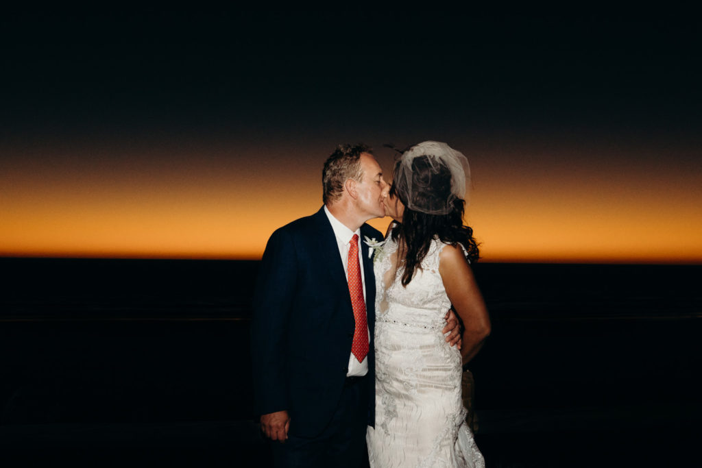 kissing wedding couple with Cable Beach sunset glow behind them