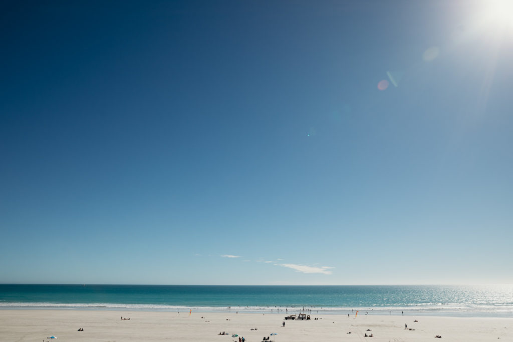 wide view across Cable Beach with sun flare peaking into the frame