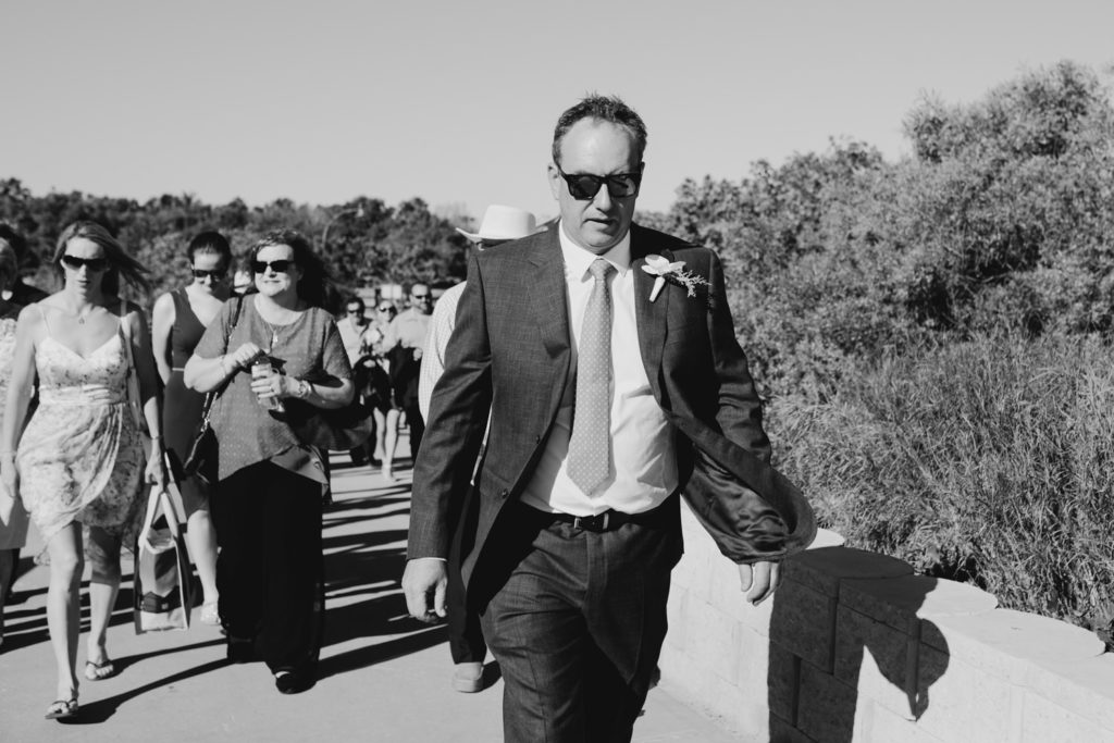groom in suit and tie wearing sunglasses is walking in front of his wedding guests