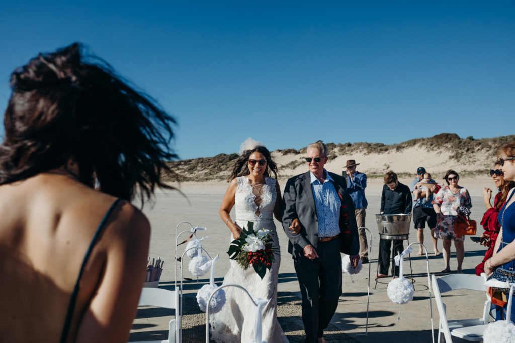 father walks his daughter down the sandy aisle at beach wedding in Broome