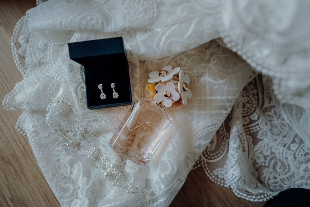 detail shot of perfume and earrings