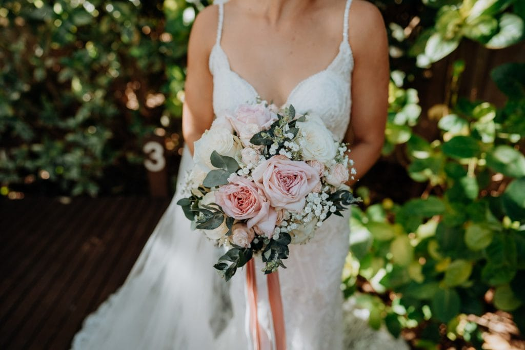 close up of bridal flower bouquet with pink roses and baby's breath