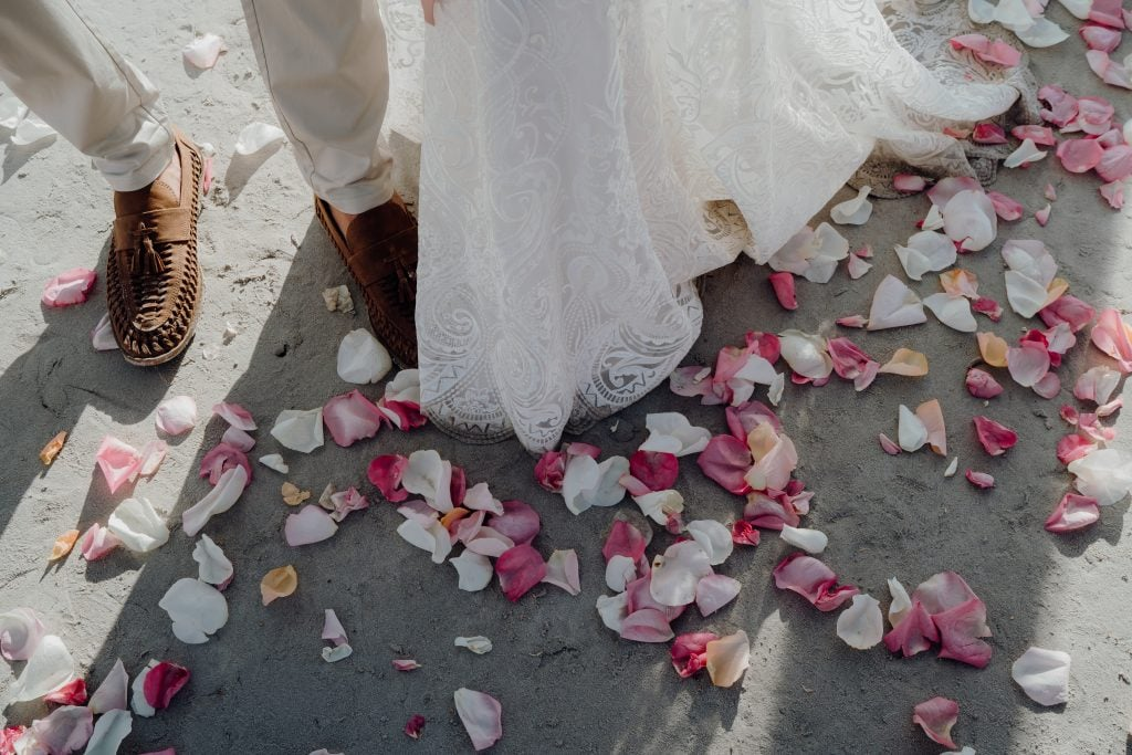 rose petals on the beach at the wedding couple's feet
