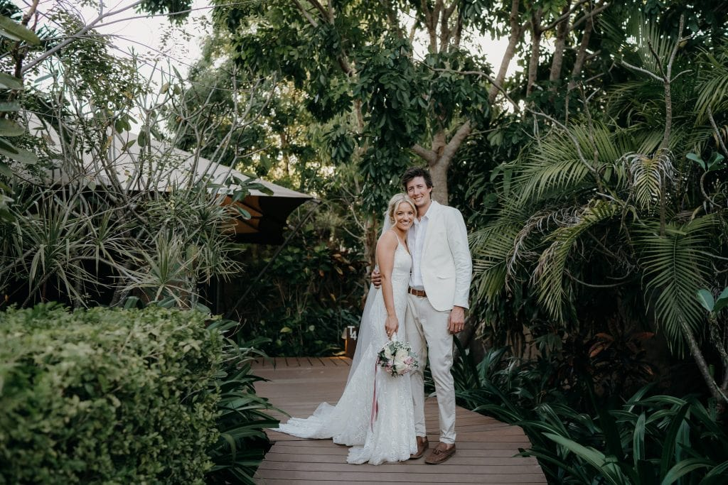 bride and groom in white attire in tropical resort in Broome