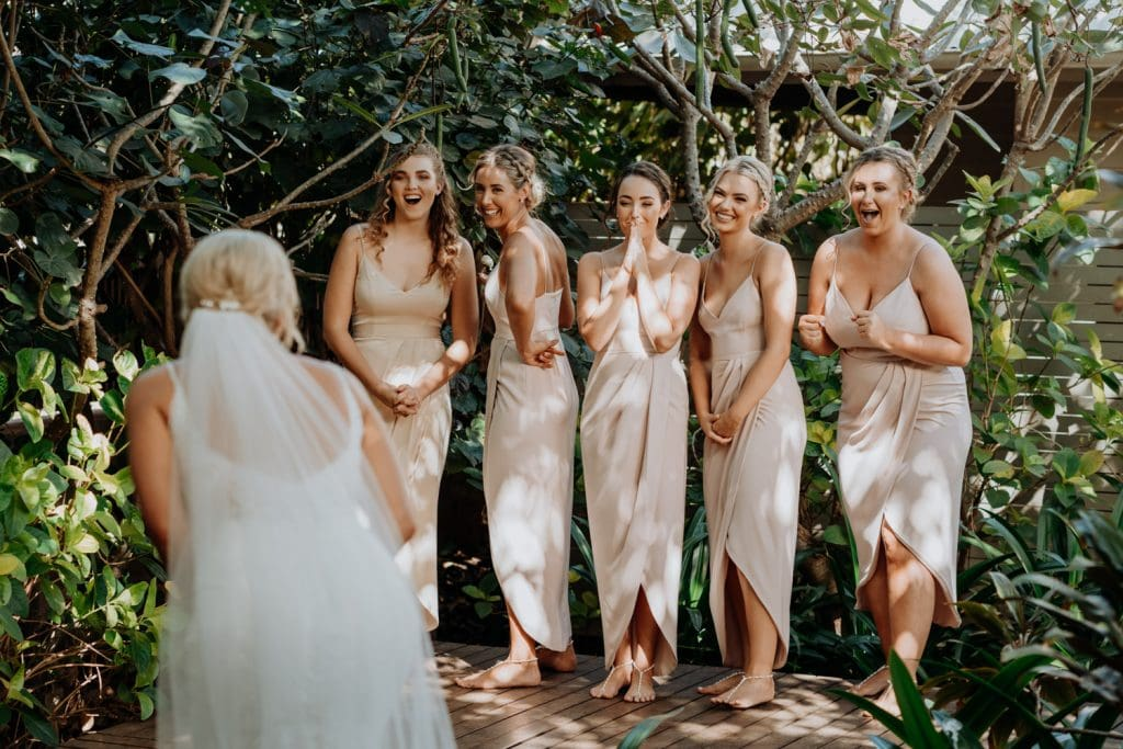 bridesmaids get to see the bride in her dress for the first time in excitement