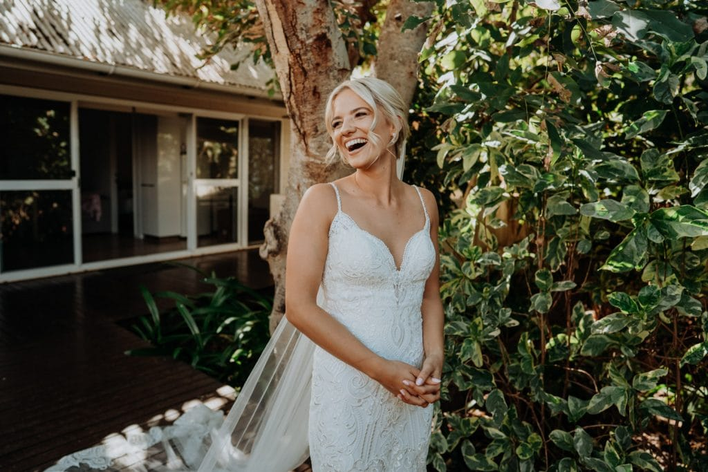 beautiful laughing bride in white wedding dress at Billi Resort in Broome