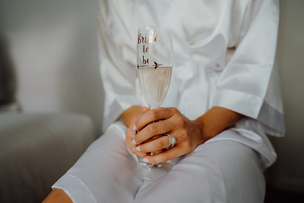 delicate female hands with engagement ring holding a glass of champagne