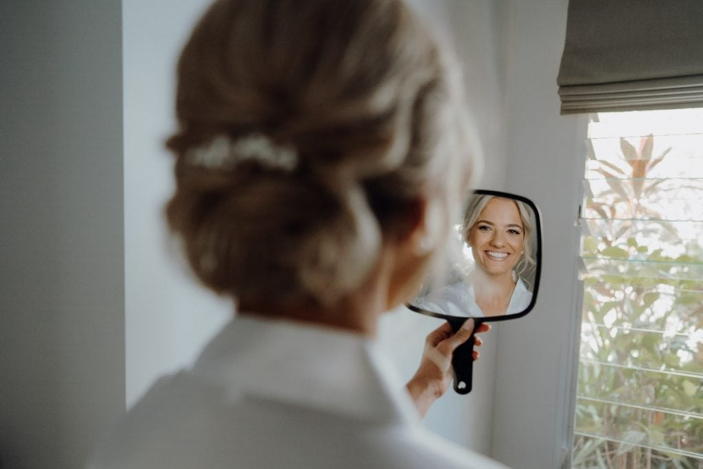 young bride looking into small mirror smiling