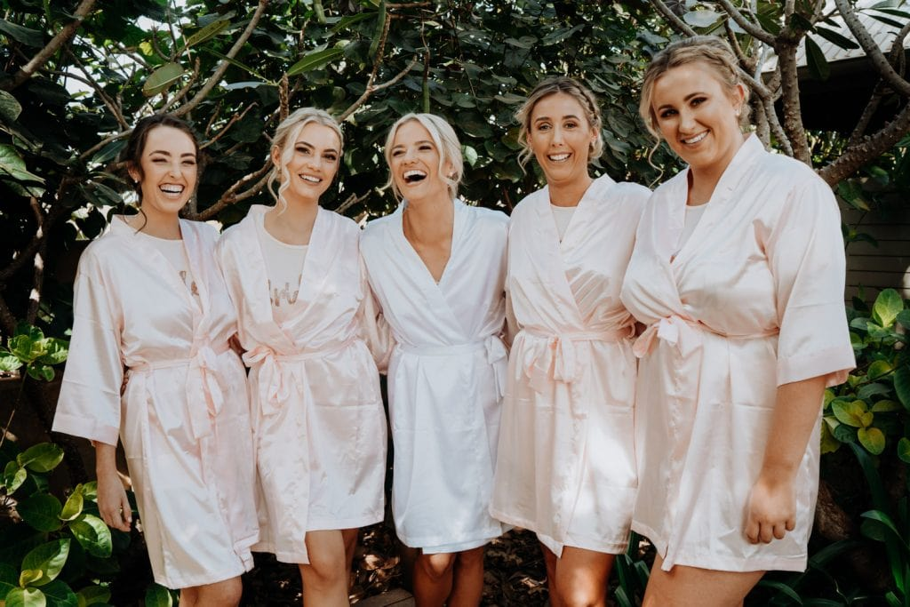 laughing bride with her four bridesmaids in silk robes
