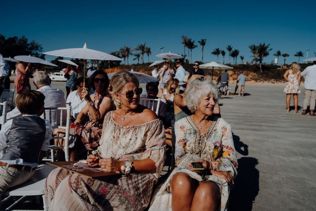 wedding guests in summer attire seated on chair at beach wedding on Cable Beach