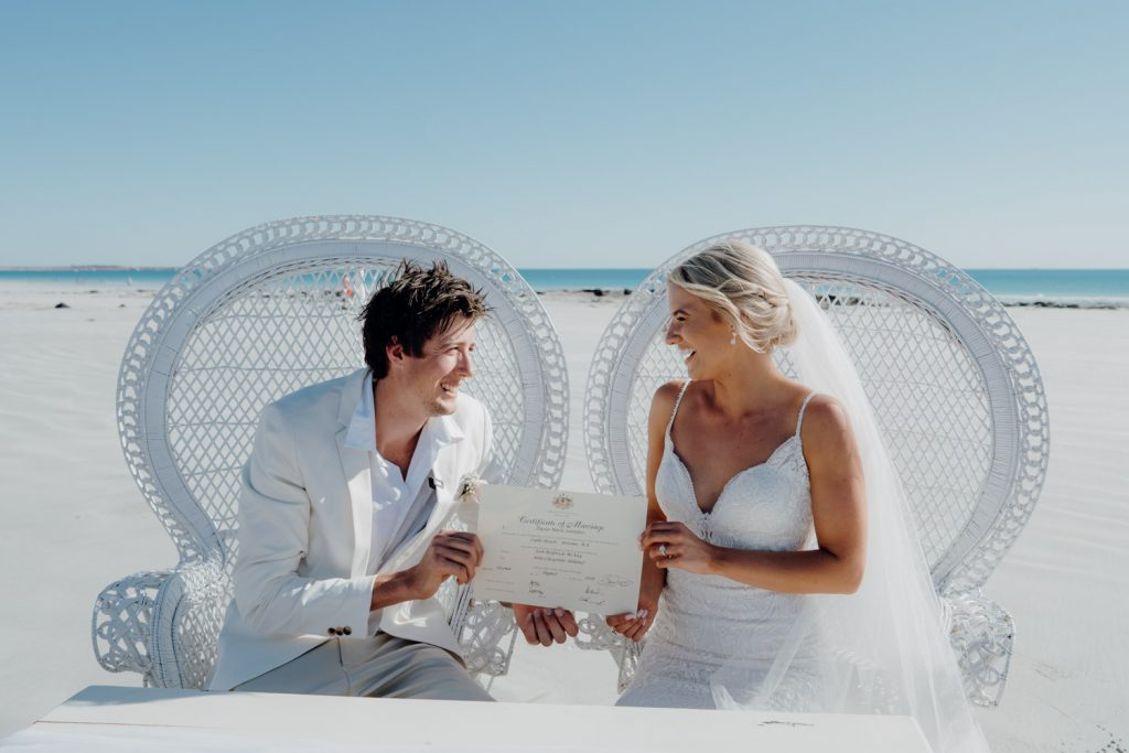 wedding couple sits in white peacock chairs and holds up their wedding certificate