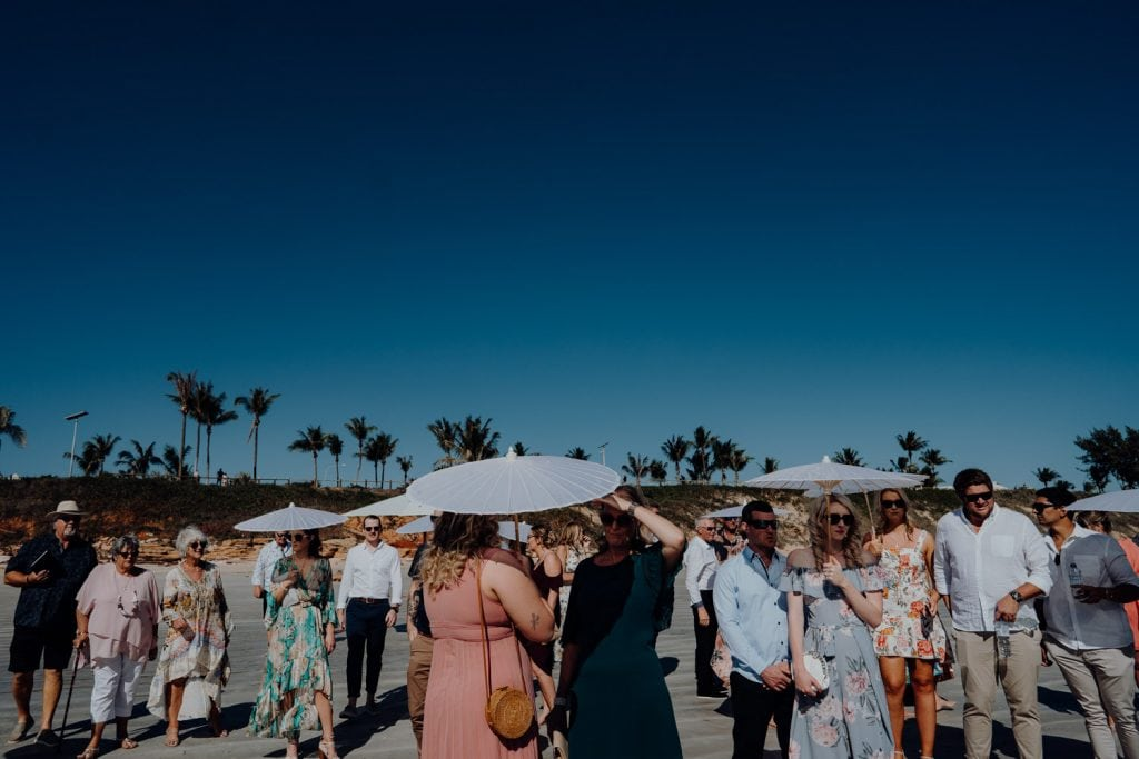 wedding guests with parasols and in summer attire at Cable Beach Wedding