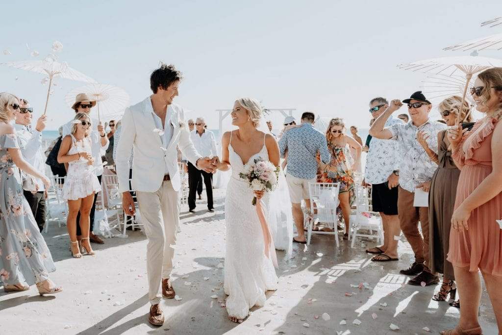 young married couple walks down the aisle while wedding guests throw flower petals on Cable Beach