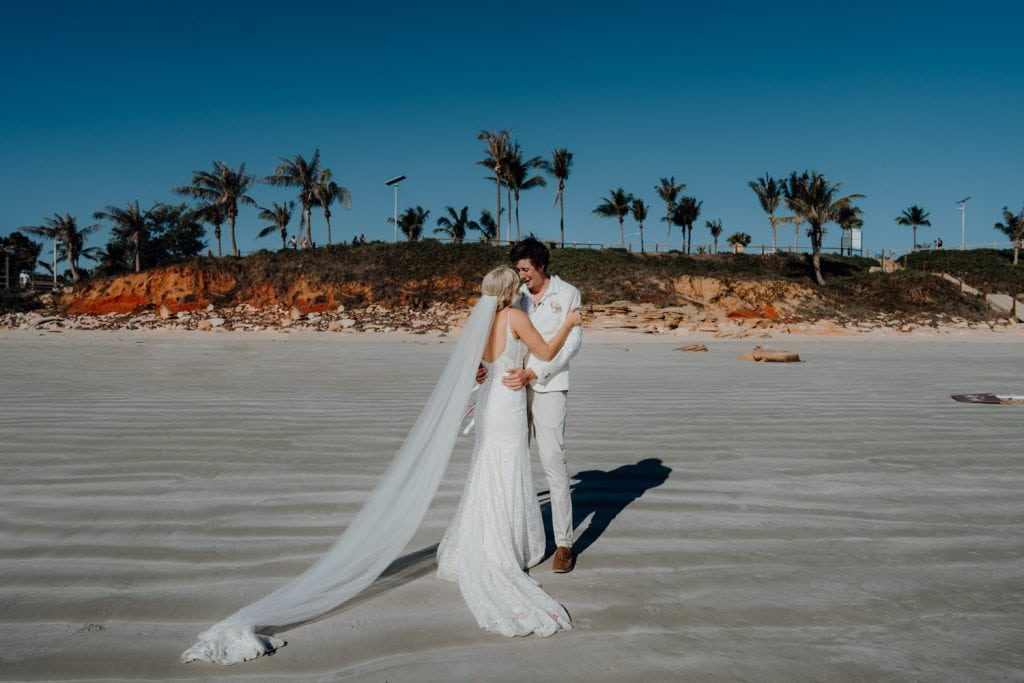 bride and groom on Cable Beach with palm tress and red cliffs as backdrop