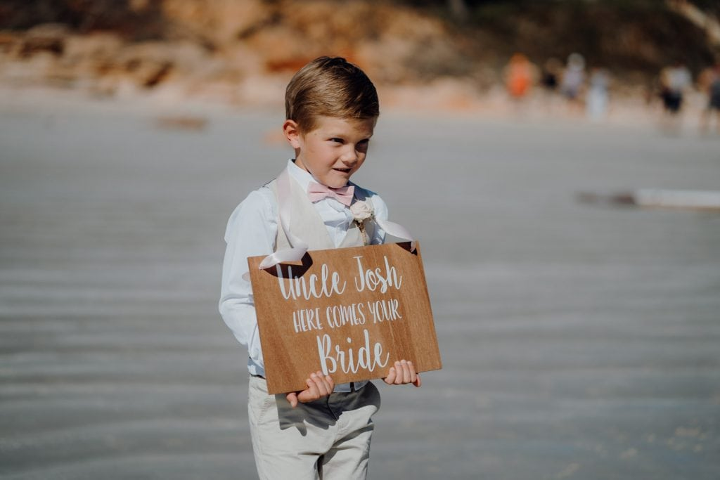 little page boy carrying a wooden sign announcing the bride