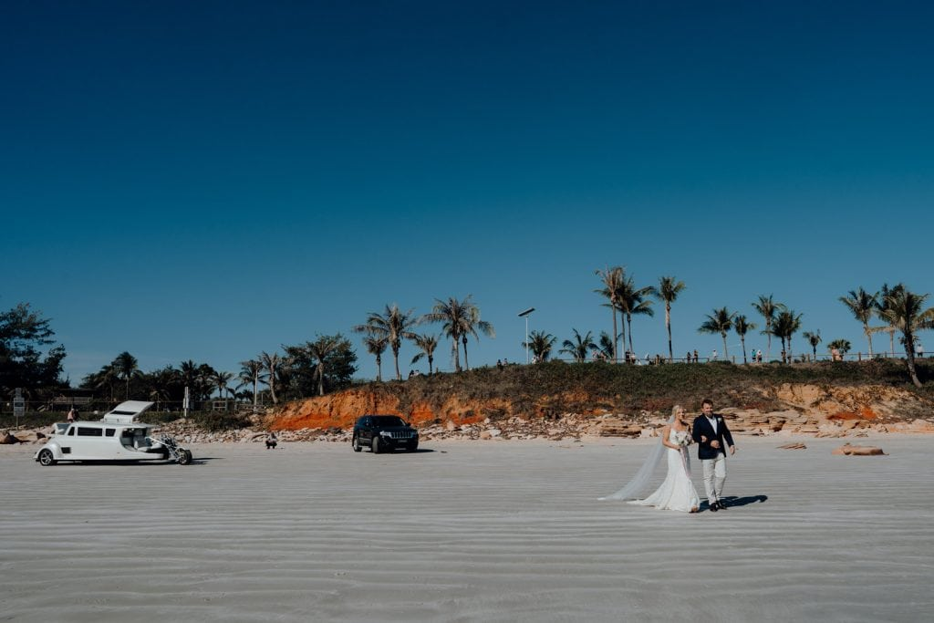 bride and her father are walking along Cable Beach with red cliffs in the background