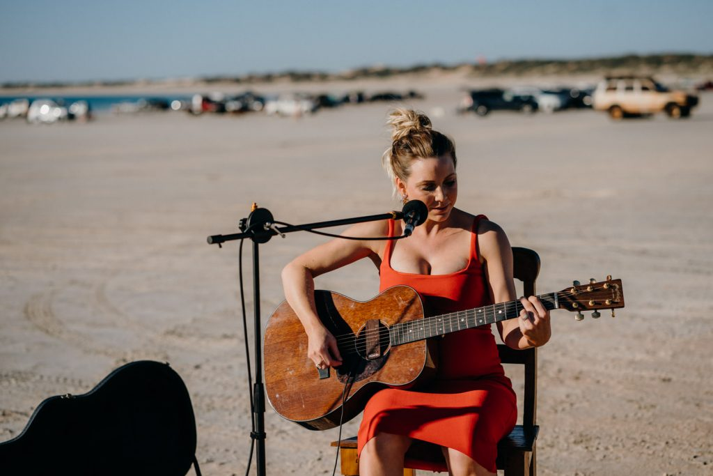 woman in red dress playing guitar and signing at Cable Beach wedding