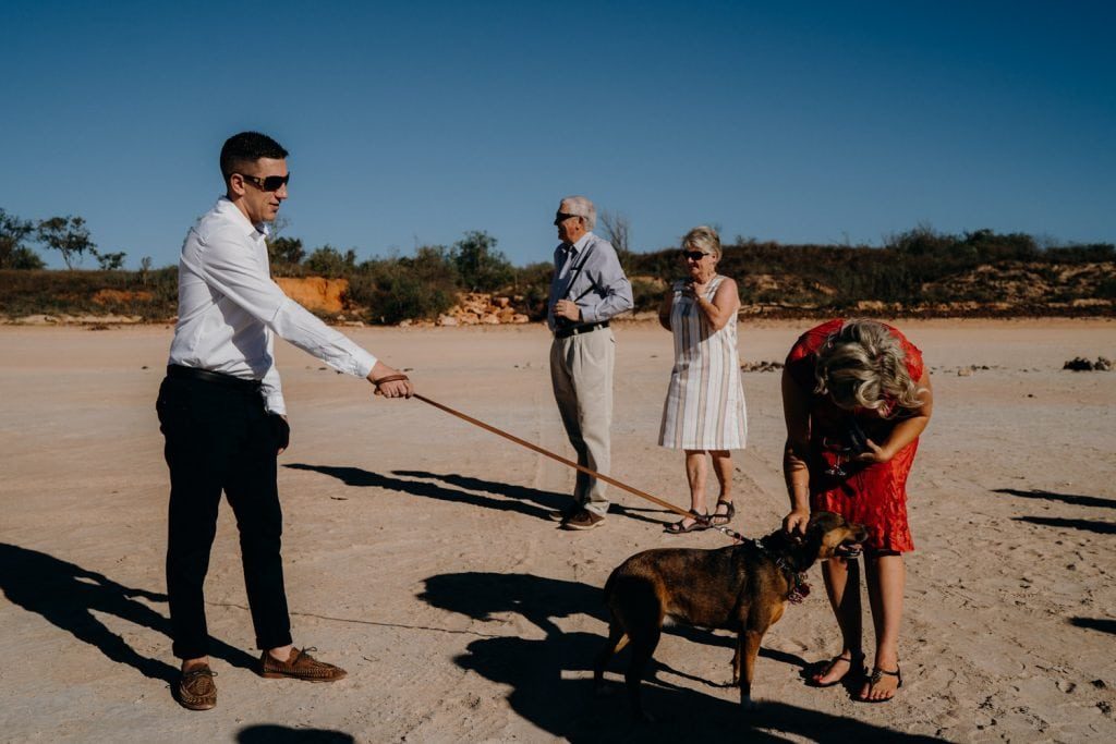 man with dog on lead and other people around it on Cable Beach at wedding