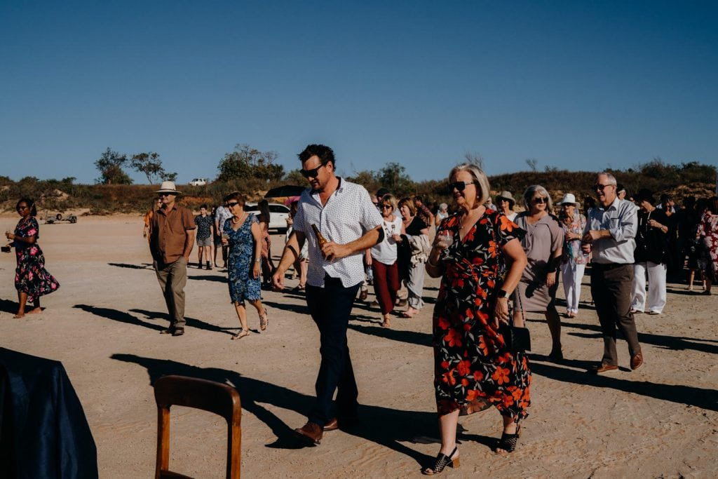 wedding guests in summer wear on Cable Beach with drinks in their hands