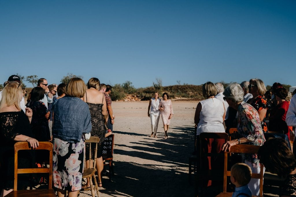 bride and her mother walking down the Cable Beach wedding aisle together with guests looking on