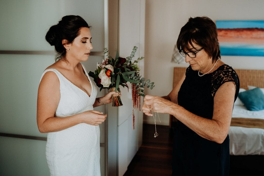 mother of the bride places necklace on her daughter's neck for her wedding