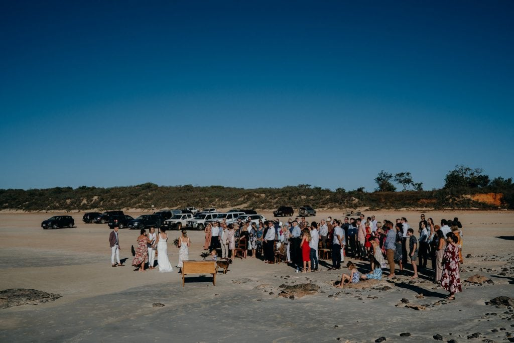 wide shot of Cable Beach wedding with blue sky and sunshine in Broome Western Australia