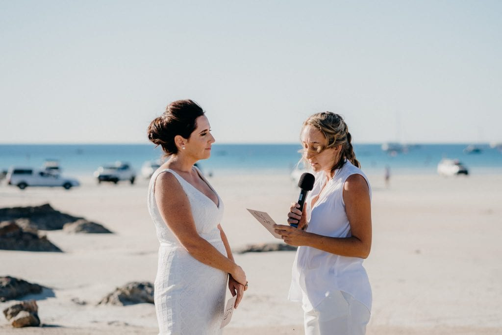 one woman reads out her wedding vows to another woman at Cable Beach wedding