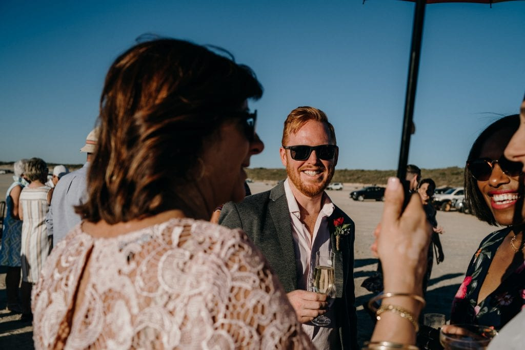 wedding guests with drinks in their hands on Cable Beach