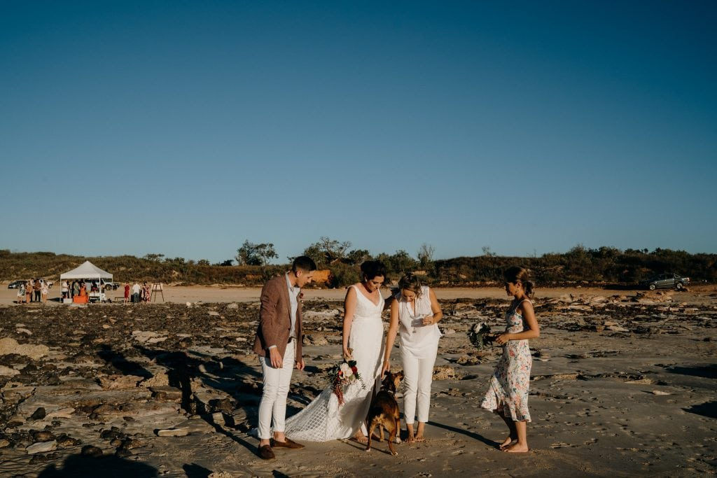 wedding couple with bridal party and dog on the beach