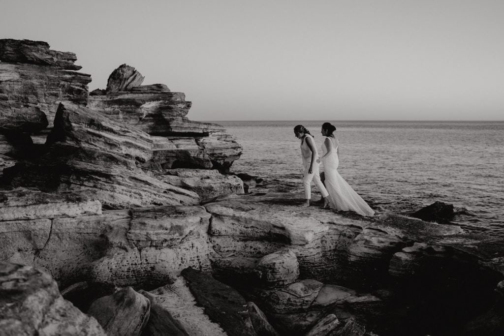 black and white image of two brides walking along cliffs near Cable Beach in Broome
