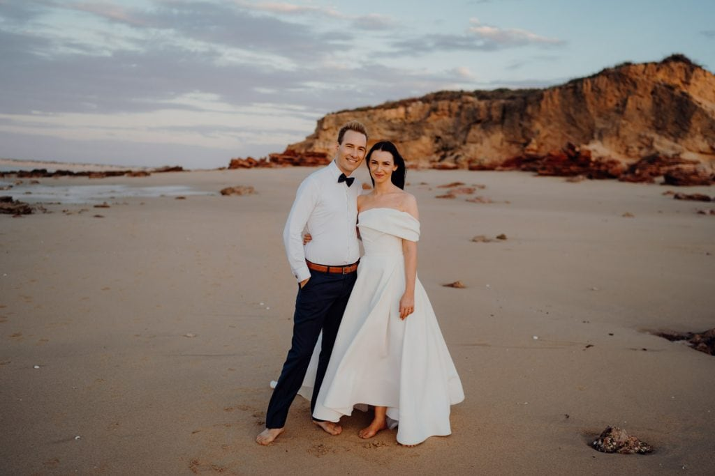 wedding couple standing arm in arm on Eco Beach for their wedding shoot