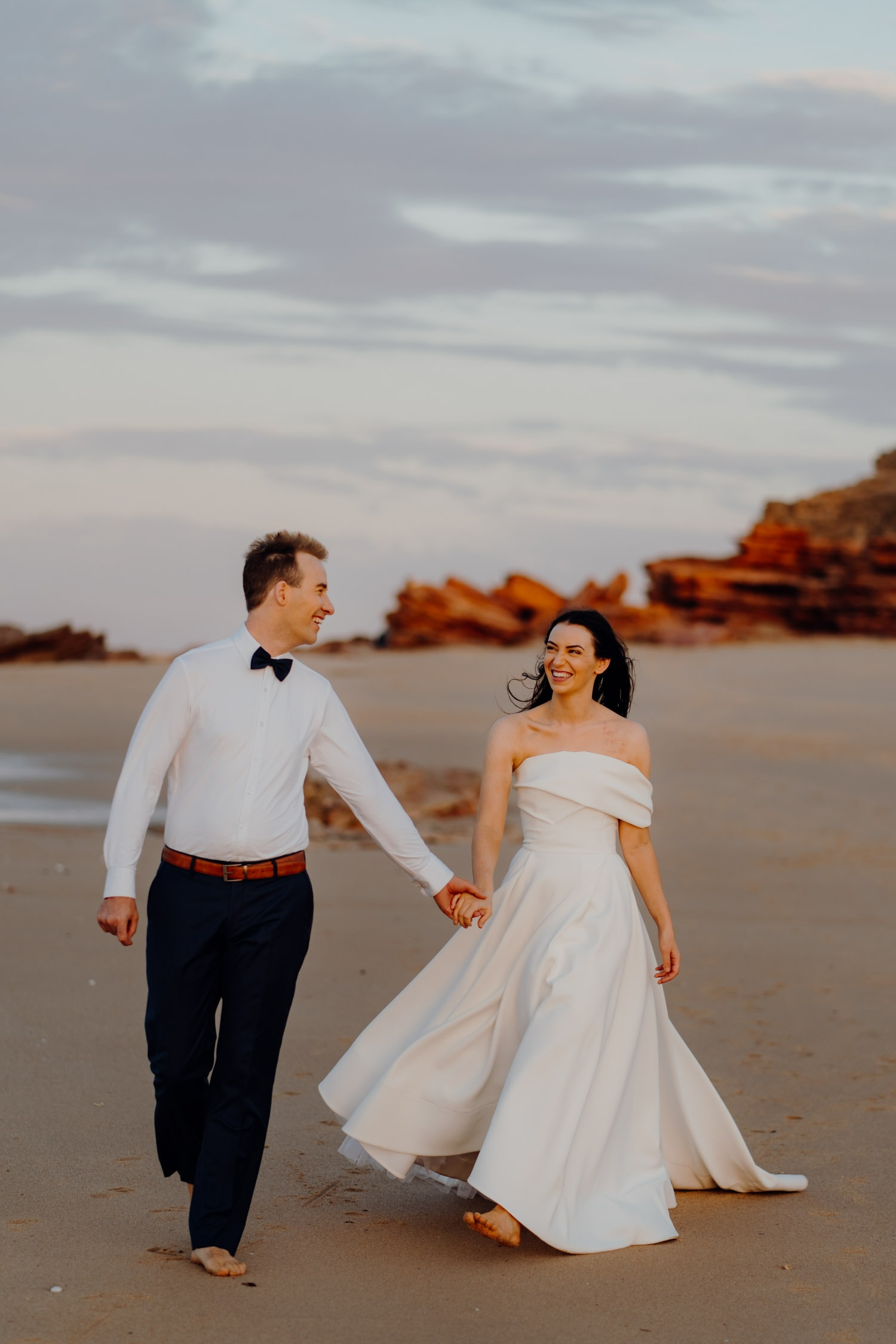 young couple walking along Eco Beach holding hands with red cliffs as backdrop