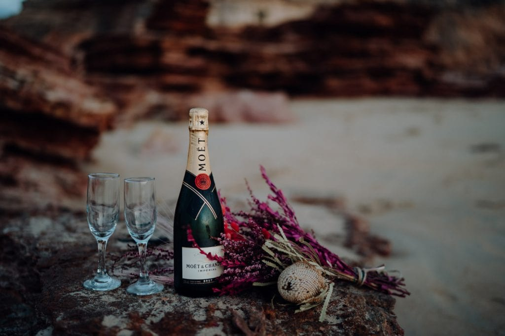 bottle of expensive champagne next to glasses and flowers on a rock at Eco Beach